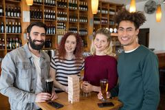 Amis ayant le verre de bière dans la barre Image stock