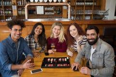 Amis ayant le verre de bière dans la barre Photos stock