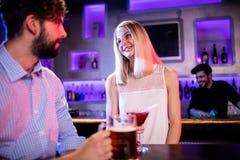 Amis ayant le verre de bière et de rouge martini au compteur de barre Images libres de droits