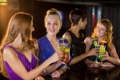 Amis ayant le verre du cocktail dans la barre Photo stock