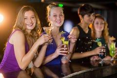 Amis ayant le verre du cocktail dans la barre Photos libres de droits