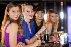 Amis ayant le verre du cocktail dans la barre Photo libre de droits