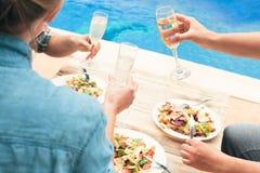 Amis ayant le vin à la partie par la piscine Photo libre de droits