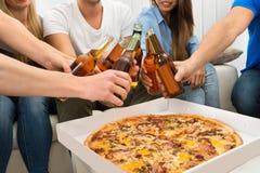 Amis ayant les bières et la pizza Photographie stock libre de droits