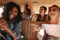 Amis ayant un bon nombre d'amusement sur le voyage par la route images stock