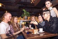 Amis ayant un café ensemble femmes et homme au café, parlant, riant Image libre de droits
