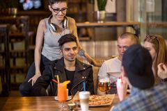 Amis ayant un café ensemble femmes et homme au café, parlant, riant Image stock