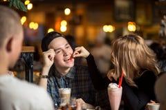 Amis ayant un café ensemble femmes et homme au café, parlant, riant Images stock