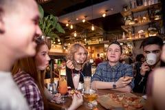 Amis ayant un café ensemble femmes et homme au café, parlant, riant Photos libres de droits
