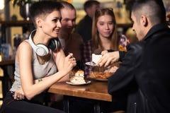 Amis ayant un café ensemble femmes et homme au café, parlant, riant Photographie stock libre de droits