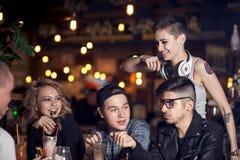 Amis ayant un café ensemble femmes et homme au café, parlant, riant Photographie stock