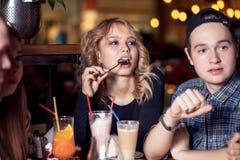 Amis ayant un café ensemble femmes et homme au café, parlant, riant Images libres de droits