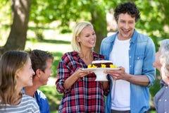Amis ayant un pique-nique avec le gâteau Photos stock