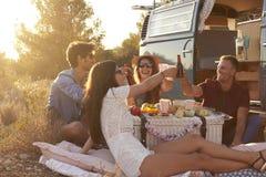 Amis ayant un pique-nique près d'un camping-car faisant un pain grillé Photo libre de droits