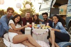 Amis ayant un pique-nique près du camping-car regardant à l'appareil-photo Image stock