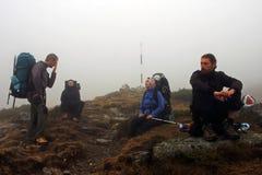 Amis ayant un repos sur leur chemin vers le haut de la montagne Image libre de droits