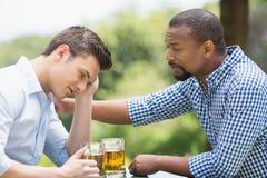 Amis ayant une conversation tout en ayant la bière Image libre de droits