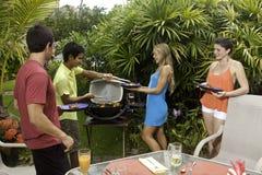 Amis ayant une partie de barbecue Photo stock