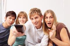 Amis ayant une petite partie à la maison Image stock