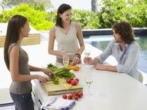 Amis ayant une vie sociale tout en préparant la nourriture à la partie supérieure du comptoir Images stock