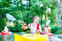 Amis barbotant avec le canoë sur la rivière Photographie stock libre de droits