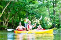Amis barbotant avec le canoë sur la rivière de forêt Image libre de droits