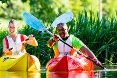Amis barbotant avec le kayak sur la rivière de forêt Photographie stock libre de droits