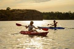 Amis barbotant des kayaks sur la belle rivière ou lac sous le ciel dramatique de soirée au coucher du soleil Image stock