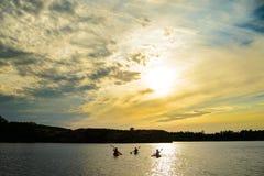 Amis barbotant des kayaks sur la belle rivière ou lac sous le ciel dramatique de soirée au coucher du soleil Images stock