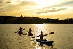 Amis barbotant des kayaks sur la belle rivière ou lac sous le ciel dramatique de soirée au coucher du soleil Photographie stock libre de droits