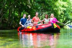 Amis barbotant sur le canot en caoutchouc à la rivière de forêt Image libre de droits