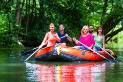 Amis barbotant sur le canot en caoutchouc à la rivière ou à la crique de forêt Image libre de droits