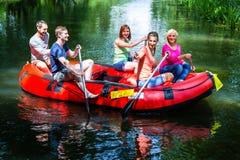 Amis barbotant sur le canot en caoutchouc à la rivière ou à la crique de forêt Photographie stock libre de droits