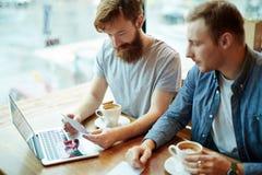 Amis barbus recueillis dans le café confortable Photographie stock libre de droits