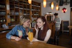 Amis bavardant au-dessus du téléphone portable tout en sirotant des cocktails photo stock