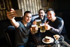 Amis beaux ayant l'amusement prenant le selfie et buvant de la bière pression dans le bar Image libre de droits