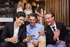 Amis beaux ayant une boisson ensemble Photo stock