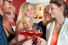 Amis blancs jetant des verres en l'air de vin rouge Photo libre de droits