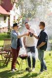 Amis buvant de la bière à la partie de barbecue d'été Image stock