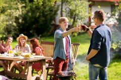 Amis buvant de la bière à la partie de barbecue d'été Images stock