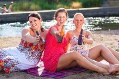 Amis buvant de la bière à la plage de rivière Photos libres de droits