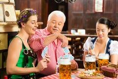 Amis buvant de la bière dans le bar bavarois jouant des cartes Image stock