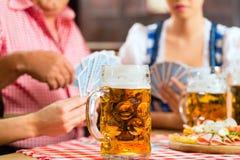 Amis buvant de la bière dans le bar bavarois jouant des cartes Photographie stock libre de droits