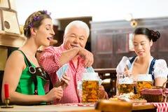 Amis buvant de la bière dans le bar bavarois jouant des cartes Photo stock