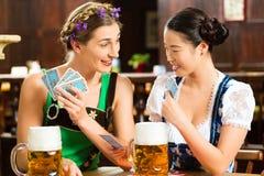Amis buvant de la bière dans le bar bavarois jouant des cartes Photographie stock