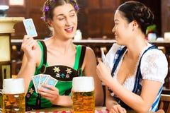 Amis buvant de la bière dans le bar bavarois jouant des cartes Photos stock