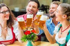 Amis buvant de la bière dans le restaurant ou le bar bavarois Photo stock