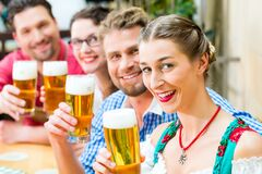 Amis buvant de la bière dans le restaurant ou le bar bavarois Photographie stock