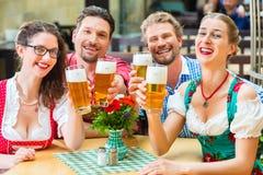 Amis buvant de la bière dans le restaurant ou le bar bavarois Image stock