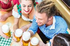 Amis buvant de la bière dans le restaurant ou le bar bavarois Photographie stock libre de droits